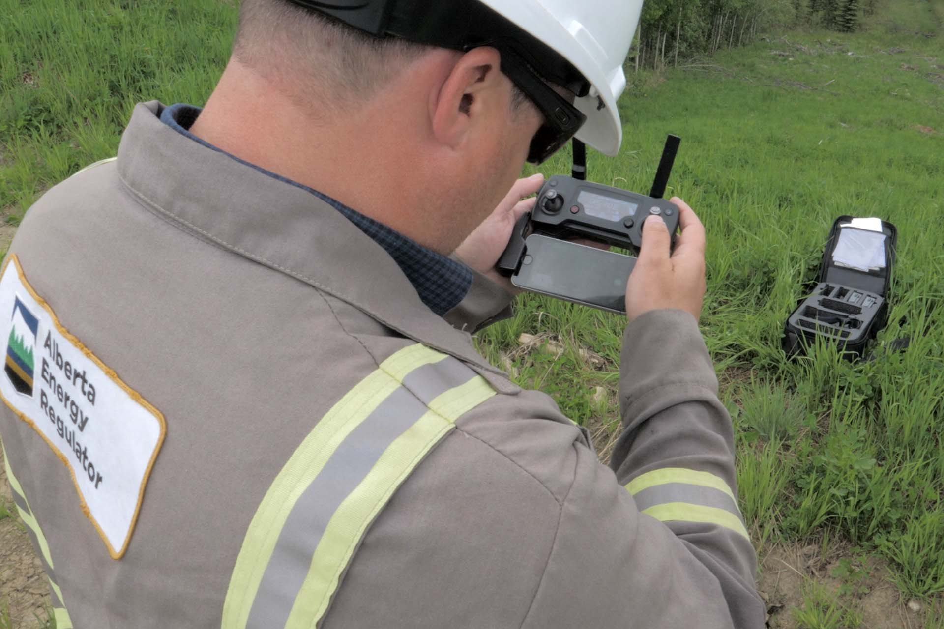 AER Field Inspector Derek Flewell operates a drone from his smart phone during an aerial inspection